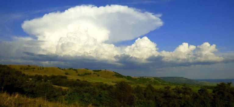 Photograph across green fields of large cumulus clouds against a blue sky with a huge cumulonimbus cloud, the top of which has spread into an anvil