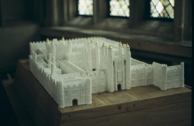 A photograph of a subtlety, in the shape of Hampton Court Palace on a table