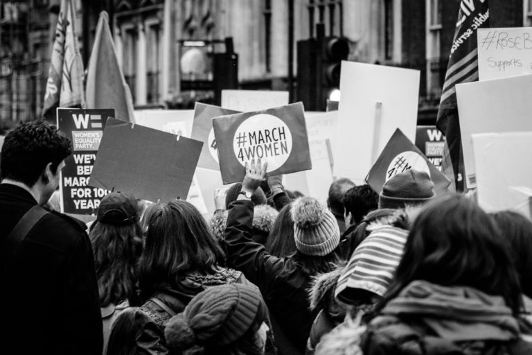 Black and White photo of a march, taken from behind. Banners say #MARCH4WOMEN