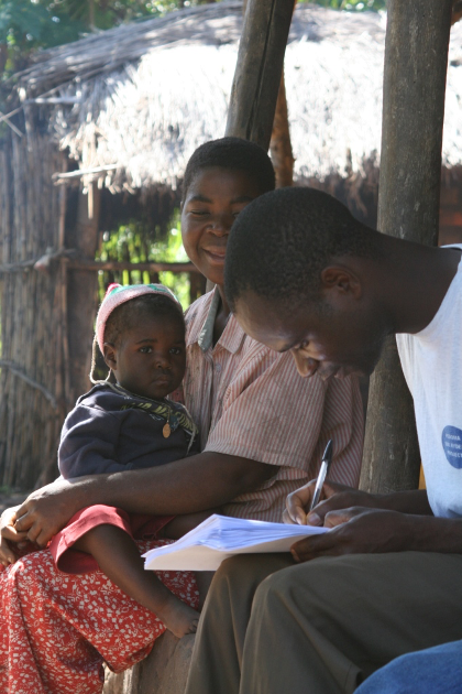 Male data collector filling out a survey form as he speaks to a research participant and her child