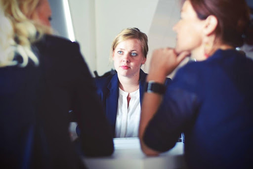 Colour photograph showing three women, one facing the camera and two with backs to the camera in what appears to be a business meeting