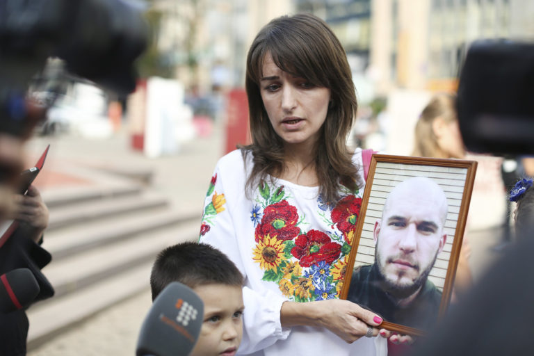A woman shows a photograph of her loved one who is missing