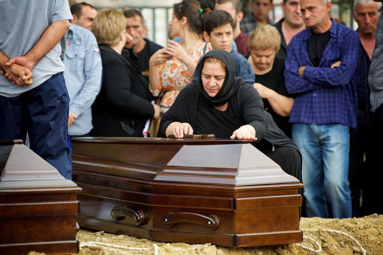 Family member of one of the 17 identified individuals bending over the coffin in grief