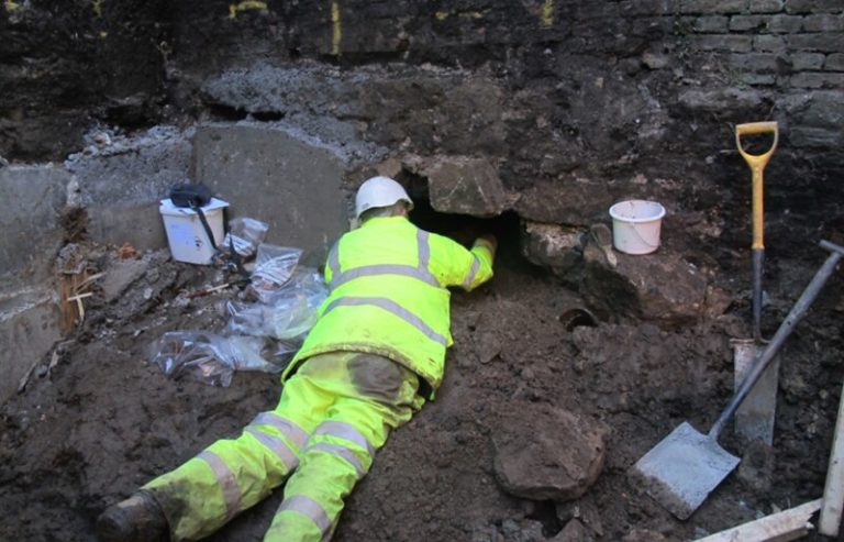 An archaeologist dressed in high visibility rainproof clothes lies on his front on piles of soil whilst reaching under a wall to excavate