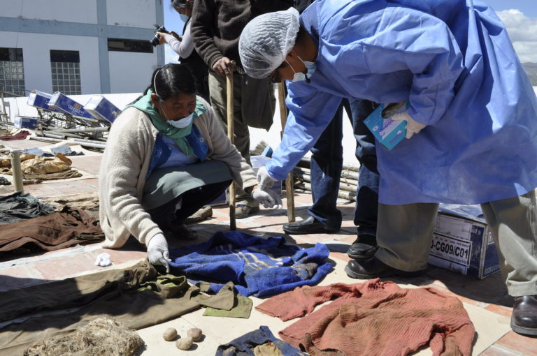 Family members sort through clothes that are laid out on the floor in an attempt to recognise those that may belong to a family member who is missing