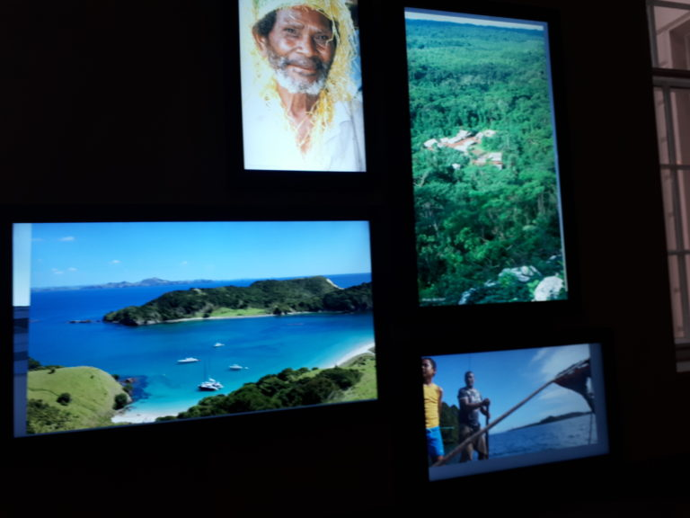 Photographic representations of Pacific islands, peoples and places, including an old man with headwrap, people fishing, and a harbour with blue sea and boats