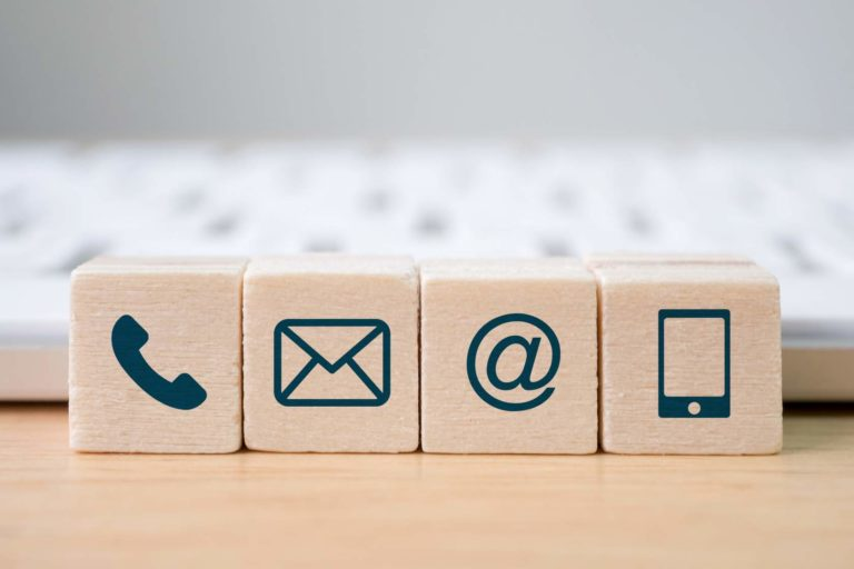 Wooden blocks with technological symbols on them, like a phone, an email and an @ sign.