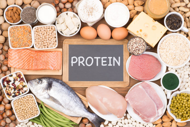 A collection of foods including fish, meat, eggs, cheese, vegetables, nuts and beans