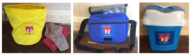 Left: Yellow bucket storage bag with a draw string top. It has the Bishesta logo on the front. The logo is Bishesta is striding into the foreground, smiling, with her arms held high. Perana stands behind Bishesta and proudly watches at her. A reusable menstrual pad and a soft cloth is laid next to the yellow bucket storage bag. Middle: Blue messenger shoulder bag, with the Bishesta logo underneath the flap. A clear plastic bag is fitted into the top of the shoulder bag. Right: a small flip top, yellow and white plastic bin.