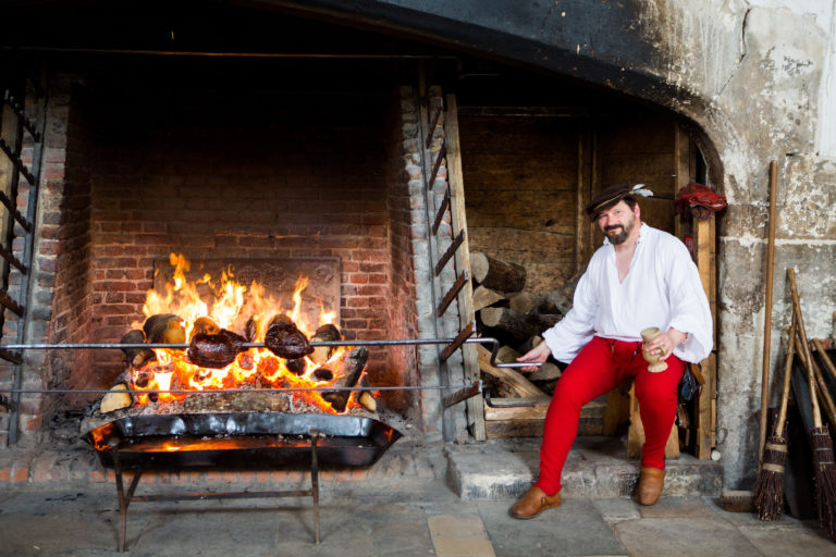 A photograph of a reenactment in a kitchen, with a cook spit-roasting meat on a large fire