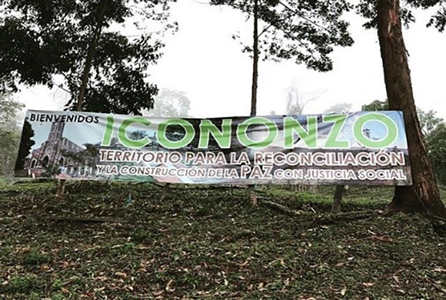 """The entrance to the FARC-EP demobilisation camp near Icononzo, Colombia. The sign reads: """"Territory for reconciliation through the constructions of peace with social justice"""". © Chiara Mizzoni"""""""
