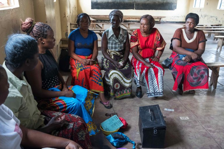 Group of Zambian women sitting in a circle for discussion about savings