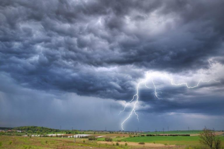 Photograph across fields with lightning coming from a dark sky