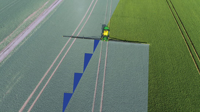 Aerial photograph of a sprayer in a field where half the field is greyed out and blue triangles show the areas that will receive inputs from an individual implementer section