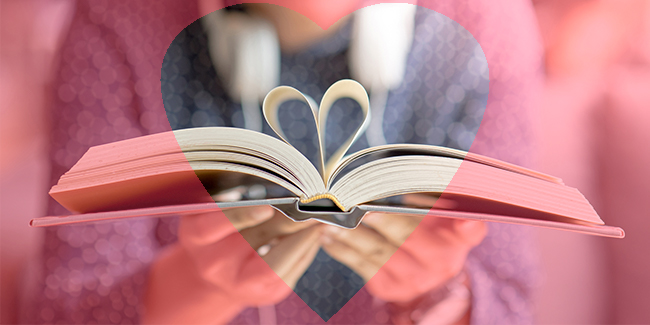Photo of someone holding a book with pages folding to a heart
