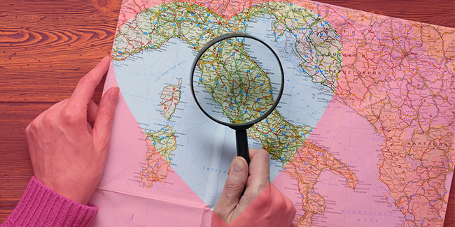Photo of someone looking at Italy on a map
