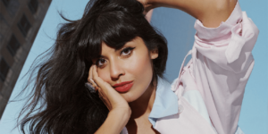 Jameela Jamil looks to camera with head resting on one hand, the other hand is on top of her head