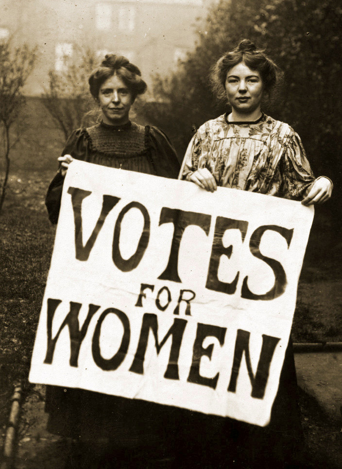 A black and white photgraph of Annie Kenney and Christabel Pankhurst holding a banner which reads 'VOTES FOR WOMEN'