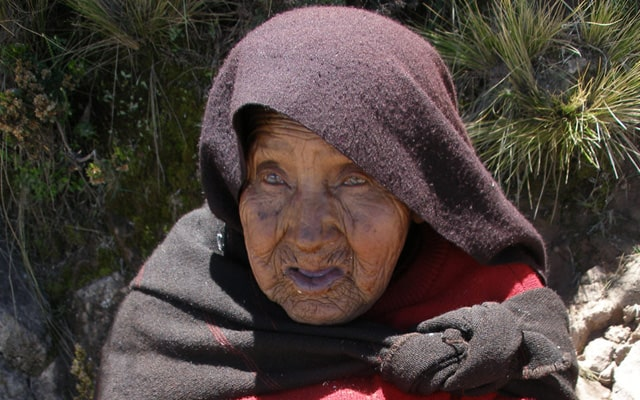 Blind woman spinning wool by hand in Taquile, Peru