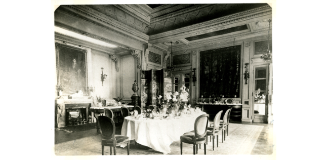 Black and white photograph of an ornate dining room from the late 19th century