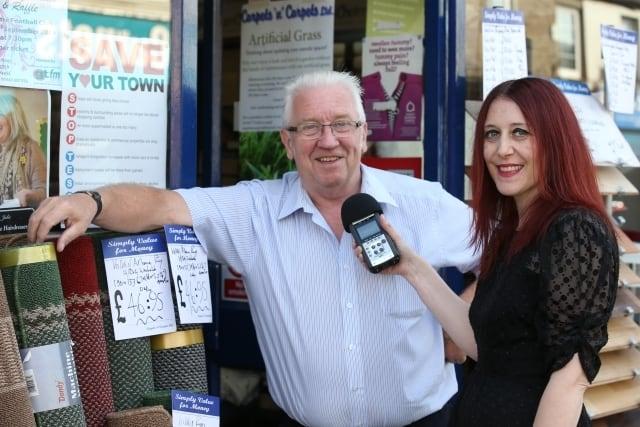A community journalist interviews a local carpet shop owner