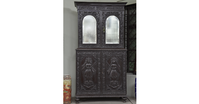 A black wooden cupboard. The upper half has mirrors and the lower half has the image of Zarathustra