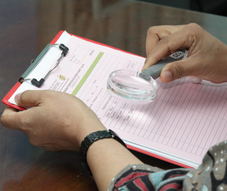 A lady uses a handheld magnifier to read a list from a clipboard