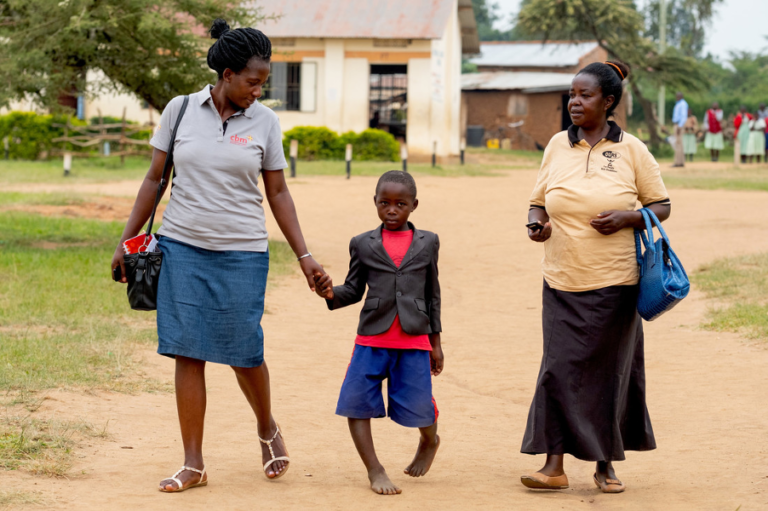 Young boy with severe bowlegs walking between two community health workers outside the school he attends in Rwemirabyo, Uganda