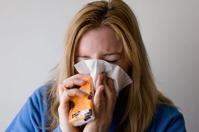 A lady with the flu sneezing into a tissue