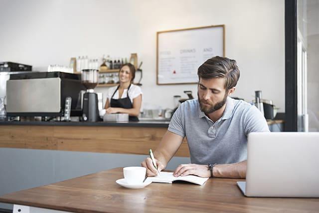 A man in a cafe jots down ideas in his writer's notebook