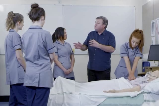 Denis Parkinson teaches four trainee nurses about resuscitation in a hospital ward in Liverpool