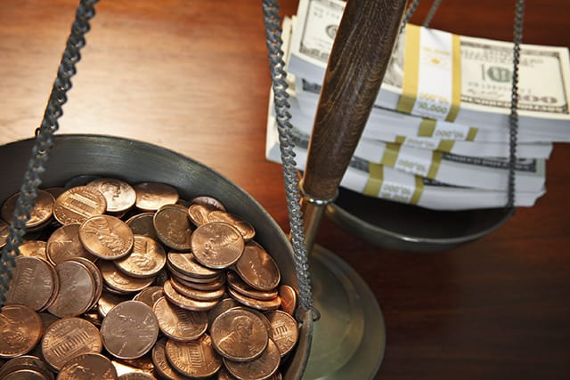 A scale with pennies on one side and a stack of bank notes on the other, representing financial inequalities